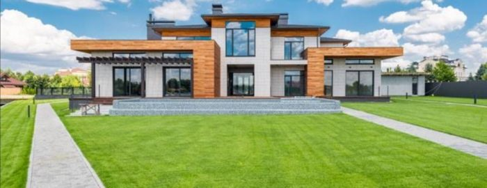 A modern house covered in windows with wooden elements and a beautiful green lawn in front of it.